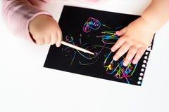 Sluit omhoog van de handen van een klein kind die op magisch kras het schilderen document met tekeningsstok trekken stock fotografie