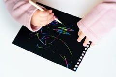 Sluit omhoog van de handen van een klein kind die op magisch kras het schilderen document met tekeningsstok trekken stock foto's