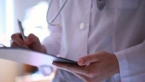 Sluit omhoog van de handen van de arts schrijvend op medische grafiek stock videobeelden