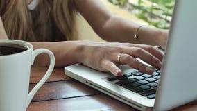 Sluit omhoog van de handen van de vrouw typend op laptop computer, in openlucht