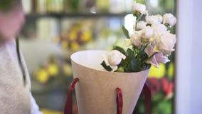 Sluit omhoog van de handen van de vrouwenbloemist zettend rozen in een kegeldoos stock video
