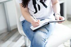 Sluit omhoog van de handen van de vrouw schrijvend in blocnote op witte moderne stoel wordt geplaatst die, freelancer stock foto's