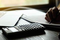 Sluit omhoog van de Handmens die financiën doen en bereken op bureau over kosten thuis bureau Besparingen, financiën en economiec royalty-vrije stock foto