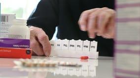 Sluit omhoog van de Hogere Mens die Medicijn organiseren in Pillenautomaat stock videobeelden