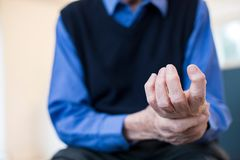 Sluit omhoog van de Hogere Mens die thuis met Artritis lijden stock afbeelding