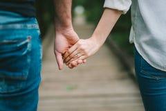 Sluit omhoog van de holdingshanden van het liefdepaar Stock Foto