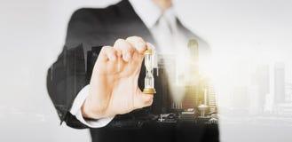 Sluit omhoog van de holdingszandloper van de zakenmanhand Stock Afbeeldingen
