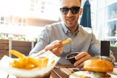 Sluit omhoog van de jonge aantrekkelijke mens die frieten en hamburger eten bij straatkoffie stock foto