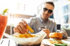 Sluit omhoog van de jonge aantrekkelijke mens die frieten en hamburger eten bij straatkoffie royalty-vrije stock foto