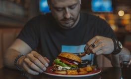 Sluit omhoog van de jonge aantrekkelijke mens die hamburger en frieten eten bij koffie stock foto's