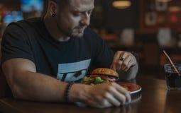 Sluit omhoog van de jonge aantrekkelijke mens die hamburger en frieten eten bij koffie stock afbeelding