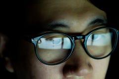Sluit omhoog van de Jonge Aziatische mens in glazen die op video's letten en Internet op technologieapparaat surfen in dark royalty-vrije stock afbeelding