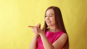 Sluit omhoog van de Jonge glimlachen van de blondevrouw groot aan de camera, die witte en perfecte tanden op gele achtergrond ope stock video