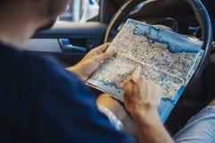 Sluit omhoog van de jonge mens die kaart achter het wiel in auto bekijken royalty-vrije stock foto's