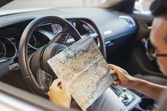 Sluit omhoog van de jonge mens die kaart achter het wiel in auto bekijken Zachte nadruk royalty-vrije stock fotografie