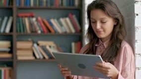 Sluit omhoog van de krullende jonge vrouw in glazen die aan het tabletapparaat werken en aan de camera bij de bibliotheek glimlac stock footage