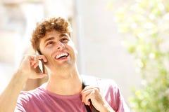 Sluit omhoog van de lachende mens die met rugzak en cellphone in park lopen Stock Afbeelding