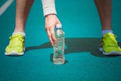 Sluit omhoog van de mannelijke plastic fles van de joggerholding water op runni royalty-vrije stock afbeeldingen