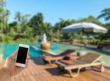 Sluit omhoog van de Mannelijke Slimme Mobiele Telefoon van de Handholding met het Lege Scherm op het Onduidelijk beeld Zwembad me royalty-vrije stock afbeeldingen