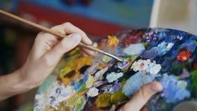 Sluit omhoog van de mengelingsverven van de vrouwen` s hand met borstel in palet in kunst-klasse stock footage