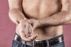 Sluit omhoog van de mens die aan pijn in zijn pols op roze achtergrond lijden gezondheidszorg en probleemconcept royalty-vrije stock afbeeldingen