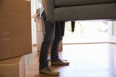 Sluit omhoog van de Mens die de Bewegende Dag van Sofa Into New Home On dragen stock afbeeldingen