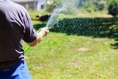 Sluit omhoog van de mens die de tuin water geven Stock Afbeelding
