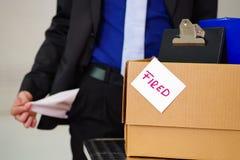 Sluit omhoog van de mens die een kostuum dragen houdend zijn lege zakken met een doos van zijn bezittingen na binnen wordt in bra stock foto