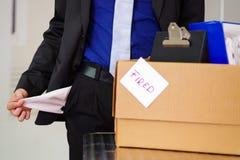 Sluit omhoog van de mens die een kostuum dragen houdend zijn lege zakken met een doos van zijn bezittingen na binnen wordt in bra stock afbeeldingen
