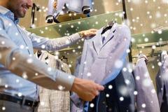 Sluit omhoog van de mens die jasje kiezen bij kledingsopslag Royalty-vrije Stock Fotografie