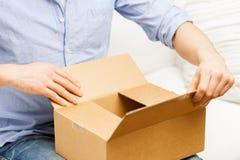 Sluit omhoog van de mens met het pakket van de kartondoos thuis Stock Foto