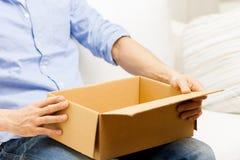 Sluit omhoog van de mens met het pakket van de kartondoos thuis Royalty-vrije Stock Fotografie