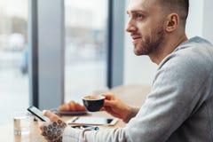 Sluit omhoog van de mens met de kop van de tatoegeringsholding van koffie en mobiele telefoon in koffie stock fotografie