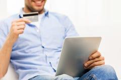 Sluit omhoog van de mens met tabletpc en creditcard Stock Afbeeldingen