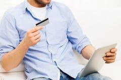 Sluit omhoog van de mens met tabletpc en creditcard Stock Foto's
