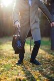 Sluit omhoog van de mensenlooppas met een zak op het hout Stock Foto's