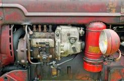 Sluit omhoog van de motor van een oude uitstekende tractor met rode roestige carrosserie en koplamp royalty-vrije stock afbeeldingen
