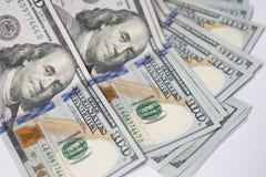 Sluit omhoog van de rekeningen van het honderd die Amerikaanse dollarsgeld op witte bedelaars worden uitgespreid Stock Foto