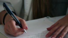 Sluit omhoog van de studentenhand schrijvend in het notaboek stock video