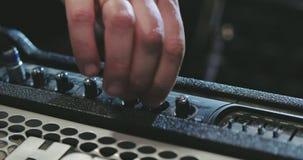 Sluit omhoog van de verbindende gitaar van de gitaristhand aan ampère stock footage