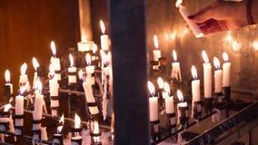 Sluit omhoog van de verlichtingskaars van de vrouwenhand op tribune in kerk stock video