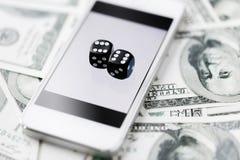 Sluit omhoog van dobbelen met slim telefoon en contant geldgeld Royalty-vrije Stock Afbeeldingen