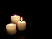 Sluit omhoog van drie aangestoken kaarsen op zwarte achtergrond. Royalty-vrije Stock Foto