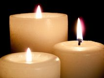 Sluit omhoog van drie aangestoken kaarsen op zwarte achtergrond. Stock Afbeelding