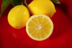 Sluit omhoog van drie citroenen op een rode plaat stock foto
