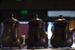 Sluit omhoog van drie koper gemaakte theepotten op verwarmer op een rij met spuiten die de waarnemer onder ogen zien stock foto