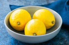 Sluit omhoog van drie rijpe gele citroenen in een grijze kom op blauwe st stock foto