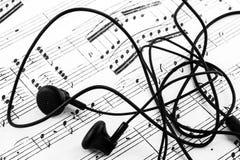 Sluit omhoog van earbuds en bladmuziek Royalty-vrije Stock Foto's