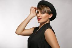 Sluit omhoog van een aantrekkelijke jonge vrouw die zwarte t-shirt, zilveren doordrongen oorringen en een buitensporige hoed drag Stock Foto's