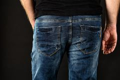 Sluit omhoog van een aardig mensenuiteinde in donkerblauwe jeans en zwart overhemd tegen zwarte achtergrond Toevallige mannelijke royalty-vrije stock foto's
